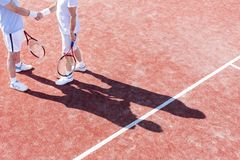Low section of mature men shaking hands while standing on tennis court during match stock photos