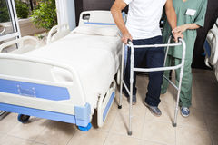 Low Section Of Nurse Helping Patient In Using Walker. Low section of female nurse helping senior male patient in using walker at rehab center Royalty Free Stock Images