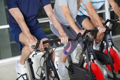 Low Section Of People On Exercise Bikes Stock Photography