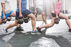 Low section of people lifting kettlebells at crossfit gym Royalty Free Stock Photography