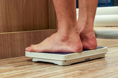 Low Section Of people Standing On Weighing Scale Royalty Free Stock Images