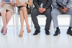 Low section of people waiting for job interview in office. Low section of business people waiting for job interview in a bright office Stock Images