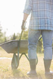 Low section rear view of man pushing wheelbarrow at garden Stock Photography