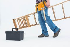 Low section of repairman carrying ladder Royalty Free Stock Photos