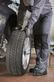Low section of repairman fixing car's tire in workshop Stock Image