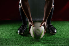 Low section of rugby player holding ball while standing against Italian Flag Stock Photography