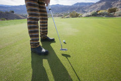 Low section of senior male golfer playing at golf course Stock Photo
