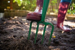 Low section of senior woman standing by garden fork on dirt Royalty Free Stock Photos
