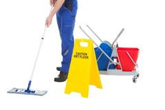 Low section of servant mopping floor by wet floor sign. Low section of male servant mopping floor by Wet Floor Sign over white background stock photography