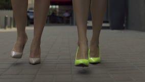 Slim female legs in high heels walking on street stock footage