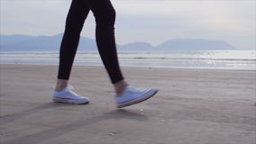 Low section slow motion of woman walking on wet shore. Slow motion film of woman walking on wet coastline. Low section of female wearing canvas shoes and pants stock footage