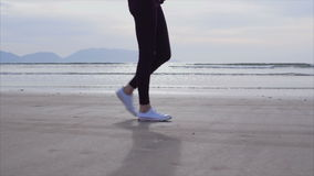 Low section slow motion of woman walking on wet shore