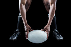 Low section of sportsman holding ball while playing rugby. Over black background royalty free stock images