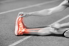 Low section of sportswoman stretching on sports track Royalty Free Stock Photos