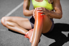 Low section of sportswoman suffering from joint pain. While sitting on track during sunny day Stock Image