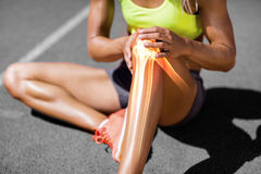 Low section of sportswoman suffering from knee pain. While sitting on track during sunny day Stock Photography
