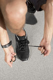 Low section of sporty man tying shoelace on street Royalty Free Stock Photo