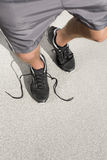 Low section of sporty man with untied shoelace standing on street Royalty Free Stock Images