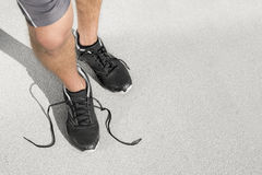 Low section of sporty man with untied shoelace standing on street Royalty Free Stock Photo