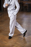 Low Section Of Tango Dancer Performing Cross Step In Restaurant. Low section of male tango dancer performing cross step on hardwood floor in restaurant Royalty Free Stock Photography