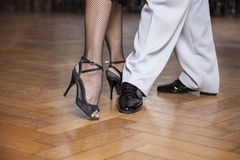 Low Section Of Tango Dancers Performing Parallel Walk. Low section of male and female tango dancers performing parallel walk in restaurant Royalty Free Stock Photo