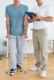 Low section of a therapist and disabled patient with reports. Low section of a male therapist and disabled patient with reports in the gym at hospital Stock Image