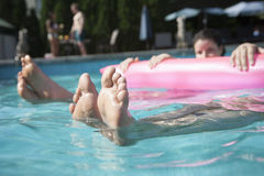Low section of two friends in a pool holding onto an inflatable raft with feet sticking out of the water Royalty Free Stock Images