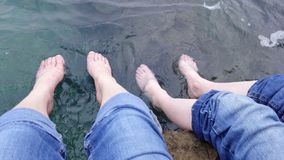 Two sets of feet paddling in the sea, Croatia stock images