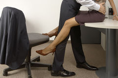 Low section view of a businessman and a businesswoman flirting in an office Stock Photo