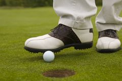 Low section view of a man putting a golf ball into a hole with a foot Royalty Free Stock Photo