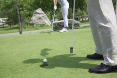 Low section view of man and woman golfing and putting on the golf course Stock Photo