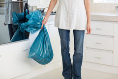 Low section of woman carrying garbage bag in kitchen Stock Photos