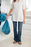 Low section of woman carrying garbage bag in kitchen Royalty Free Stock Image