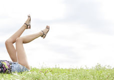 Low section of woman with feet up lying on grass against sky Stock Image