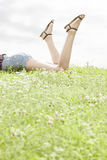 Low section of woman lying on grass against sky Royalty Free Stock Image