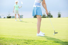 Low section of woman playing golf with female friend Royalty Free Stock Photography