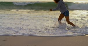 Low section of woman playing with sea waves on the beach 4k. Low section of woman playing with sea waves on the beach. She is having fun 4k stock video