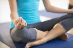 Low Section Of Woman Practicing Yoga At Gym. Low section of mid adult woman practicing yoga while sitting on exercise mat at gym Royalty Free Stock Photos