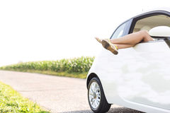 Low section of woman relaxing in car on country road Stock Photo