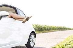 Low section of woman relaxing in car on country road. Low section of women relaxing in car on country road Royalty Free Stock Photo