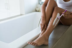 Low section of woman shaving leg in bathroom. Low section of young woman shaving leg in bathroom Royalty Free Stock Photos