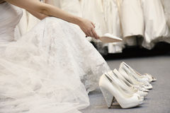 Low section of woman sitting with variety of footwear in bridal boutique. Low section of women sitting with variety of footwear in bridal boutique Royalty Free Stock Image