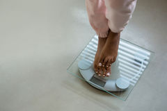 Low section of woman standing on bathroom scale. At home royalty free stock image