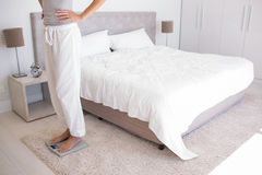 Low section of a woman standing on scale in bedroom Stock Photo