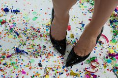Woman standing wearing black heels standing on the confetties Royalty Free Stock Photography