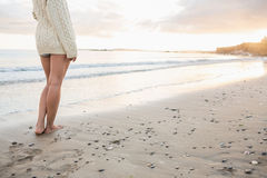 Low section of a woman in sweater standing on beach Royalty Free Stock Photos