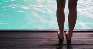 Low section of woman jumping into swimming pool