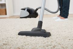 Low section of woman vacuuming floor Stock Image