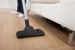 Low section of woman vacuuming floor. Low section of woman vacuuming hardwood floor at home Stock Image