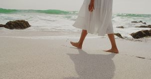 Low section of woman walking barefoot on a sunny day at beach 4k. Low section of woman walking barefoot on a sunny day at beach. Sea waves and rock in the stock video footage